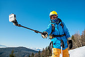 Male skier taking a selfie using his action camera and monopod in winter sunny day at ski resort