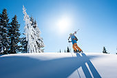 Full length shot of a male skier on top of the mountain with his skis on his shoulder on a sunny winter day sunlight nature recreation skiing resort lifestyle sportive concept