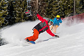 Active people enjoy riding and skiing in the mountains at winter ski resort. Male snowboarder skiing on the snowy slope and professional skier cameraman shooting him by action camera on monopod