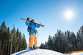 Full length shot of a skier standing on top of a snowy slope in the mountains, raising his arms in the air, enjoying beautiful sunny winter day at winter resort