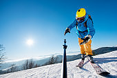 Male skier dropping his camera on monopod while taking a selfie in the mountains failure concept