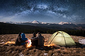 Silhouette of four people - two romantic couples are sitting together beside camp and tent under beautiful night sky full of stars and milky way. On the background snow-covered mountains. Rear view