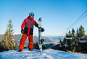 Full length shot of a snowboarder standing with his snowboard on the top of the mountain after riding at winter ski resort in the evening. Mountains, forests, ski lift and blue sky on the background