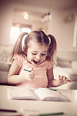 Little girl drawing and expressive positive emotion. Close up.