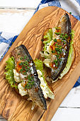 Grilled mackerel on toast with salad, scrambled eggs, onions, chives and chili sauce
