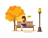 Girl resting in autumn park, communicates on phone through messengers