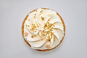 Cupcake with cream and gold confectionery sprinkling.