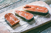 pieces of red fish in flour on a cutting board
