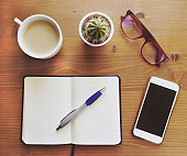 Blank notebook with pen, glasses, coffee and cactus on wooden table