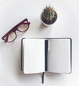 Blank notebook with pen, glasses and cactus on white table