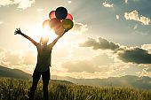 Cheering young woman jumping on grassland with colored balloons