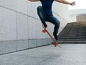 female skateboarder jumping on city with skateboard