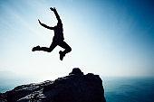 free female hiker jumping on sunrise seaside cliff edge