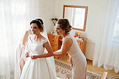 Bridesmaids helping gorgeous bride to dress up and get ready for her wedding ceremony.