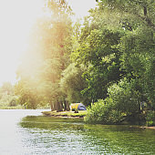 Tent near a beautiful lake, summer campsite, family vacation concept