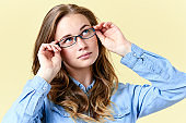 Beautiful redhead teenager girl with freckles wearing reading glasses, smiling teen portrait on yellow background