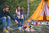 Beautiful couple, sitting, camping around the campfire. On the background with a orange tent.