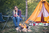 Woman traveler resting by the fire on the background of a tent