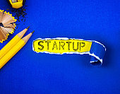 the yellow pencil on Torn blue Paper and STARTUP word with a  yellow paper background