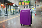 Suitcase on wheels standing on the floor in modern airport terminal. Copy space