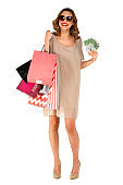 Smiling woman in dress holding money posing with shopping bags