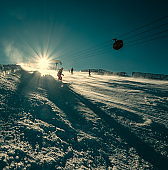 Skier slides down on the snow slope - sunny day at ski resort