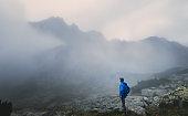 Hiker traveler in foggy mountains