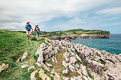 Couple backpacker travelers walk on ocean rocky coast