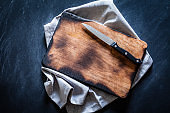 Old wooden cutting board with kitchen knife