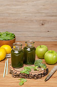 Green fresh leafy greens smoothie in glass jar, spinach leaves, apple, broccoli and lemon.
