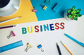 Business word on desk office background with supplies.