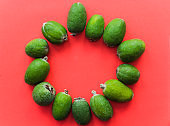 Fresh bright feijoa fruits on a red backround