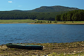 landscape of the Ural mountains, lake and an old boat