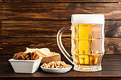 glass of cold frothy lager beer and snacks on wooden table
