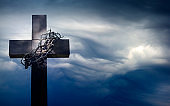 Easter cross with crown of thorns against blue sky abstract background with empty space