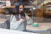 smiling young woman using mobile phone in cafe