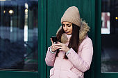portrait of young woman in a pink jacket and a cap using smartphone