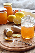 Homemade ginger and lemon jam on wooden background. Natural products to support the immune system in winter. Herbal medicine, healthy food.