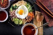 BI Bim Bap, Rice with Mixed Vegetables, top view with Hot Sauce in Cast Iron Pot
