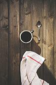 Coffee in enamel mug on wooden background