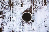 Coffee mug on snowy wooden table, outdoors