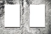 Two vertical hanged white billboard or empty blank canvas on city concrete wall background
