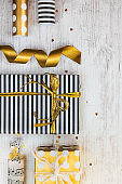 Gift boxes wrapped in black and white striped and golden dotted paper and wrapping materials on a white wood old background.