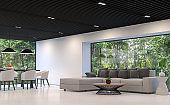 Modern black and white living room and dining room with forest view 3d rendering image