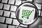 Internet shopping. Financial Planning. Computer keyboard with shopping cart icon key enlarged by a magnifying glass.