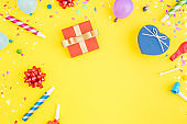 Colorful celebration pattern with various party confetti, balloons, gift box on yellow background