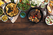 Grilled steak, grilled vegetables, potatoes, salad, different snacks and homemade lemonade on rustic wooden table with border, top view