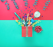 Red gift box with various party confetti, balloons, streamers, noisemakers and decoration on a multicolored background