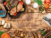 Appetizing barbecued steak, sausages and grilled vegetables on a wooden picnic table with copy space