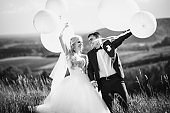 Black and white. Wedding. Wedding day. Happy, smiling newlyweds with helium balloons having fun after wedding ceremony. Wedding concept. Marriage
